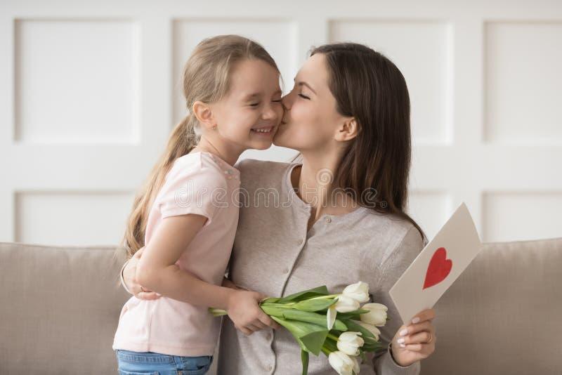 Moder som kysser uttrycklig tacksamhet för liten dotter för blommor och vykort royaltyfri fotografi