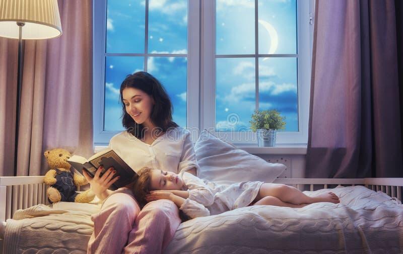 Moder som läser en bok royaltyfri foto