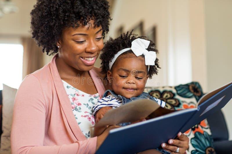 Moder som läser en bok till hennes liten flicka arkivfoton