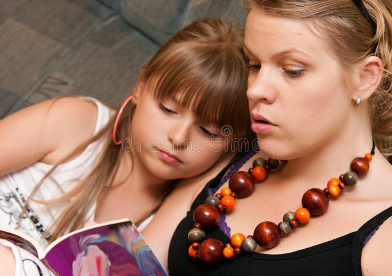 Moder som läser till dottern royaltyfri foto