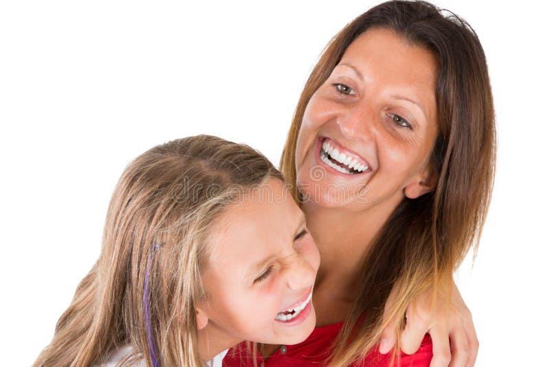 Moder som ler att skratta med hennes lycklig dotter som är rolig och arkivbilder