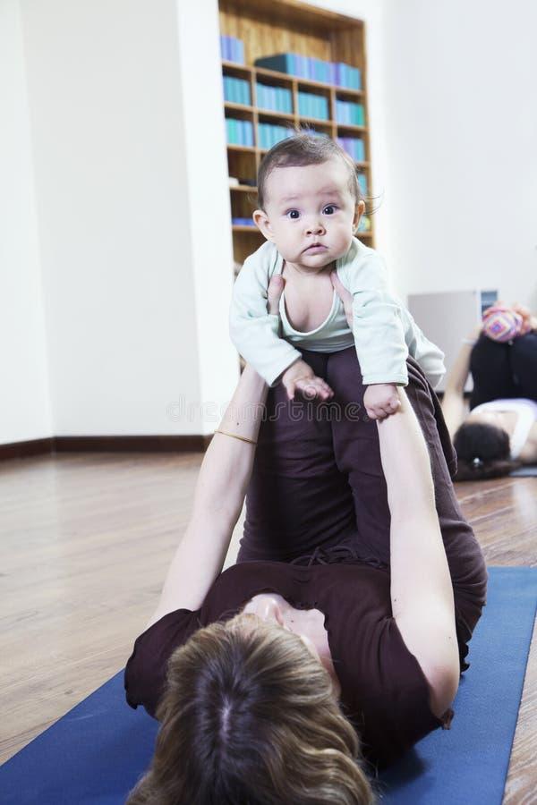 Moder som ligger på baksida, och innehav som hon behandla som ett barn under en yogagrupp royaltyfria bilder