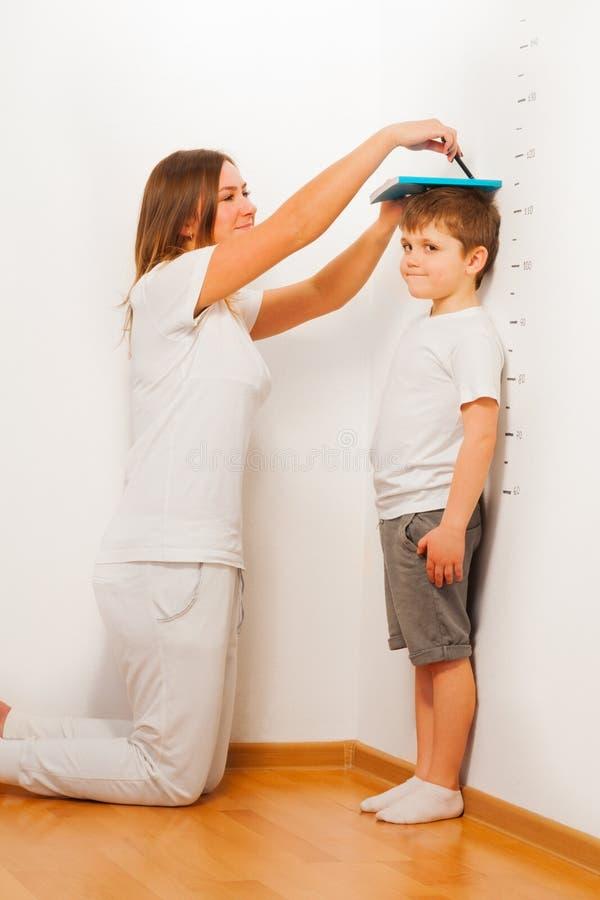 Moder som mäter hennes sons höjd mot väggen royaltyfri fotografi