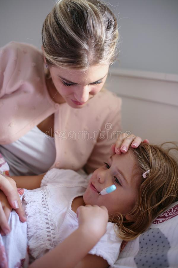 Moder som mäter temperaturdottern royaltyfri foto