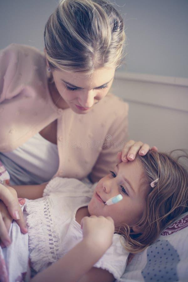 Moder som mäter temperaturdottern royaltyfria foton