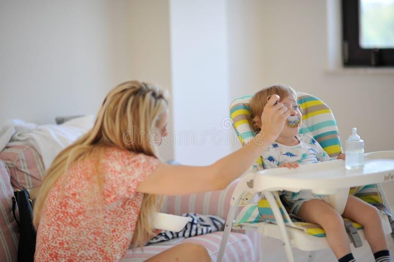 Moder som matar behandla som ett barn fotografering för bildbyråer