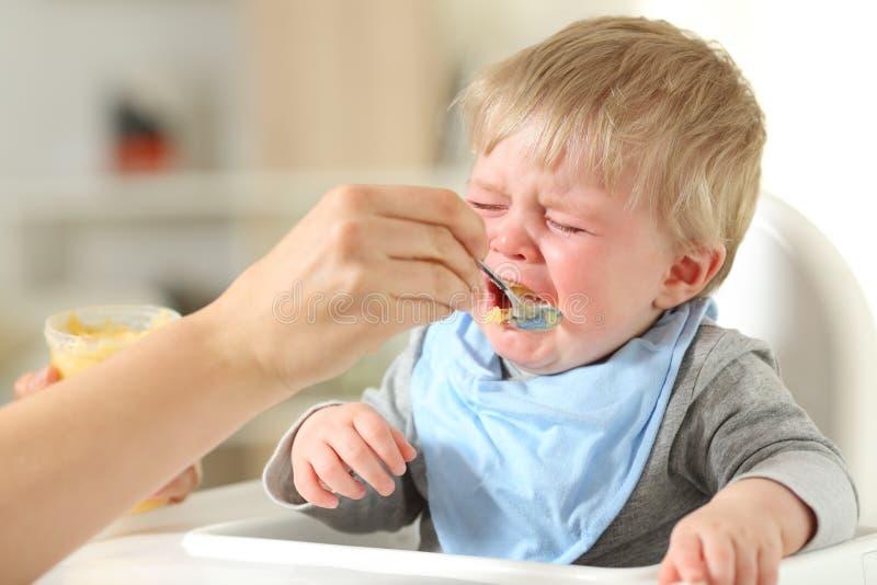 Moder som matar hans son som gråter arkivfoton