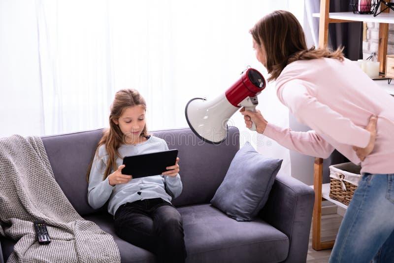 Moder som ropar till och med megafonen p? flickan som anv?nder den Digital minnestavlan royaltyfri foto