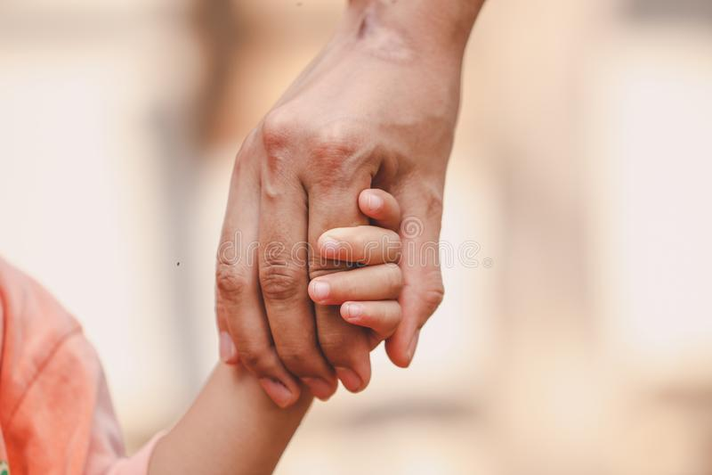 Moder som rymmer ett barns hand p? suddig bokehbakgrund arkivfoton