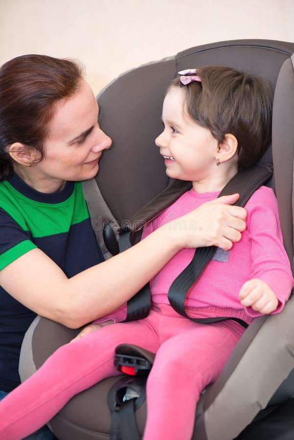 Moder som s?krar dottern i bils?tet som isoleras arkivbild