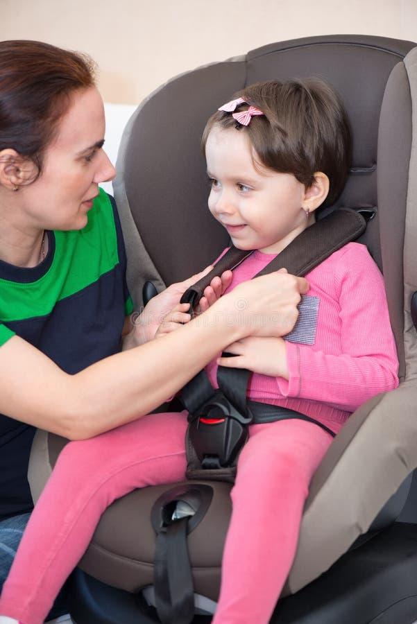 Moder som säkrar dottern i bilsätet, royaltyfria bilder