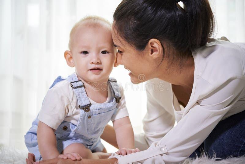 Moder som ser barnet med f?r?lskelse royaltyfria bilder