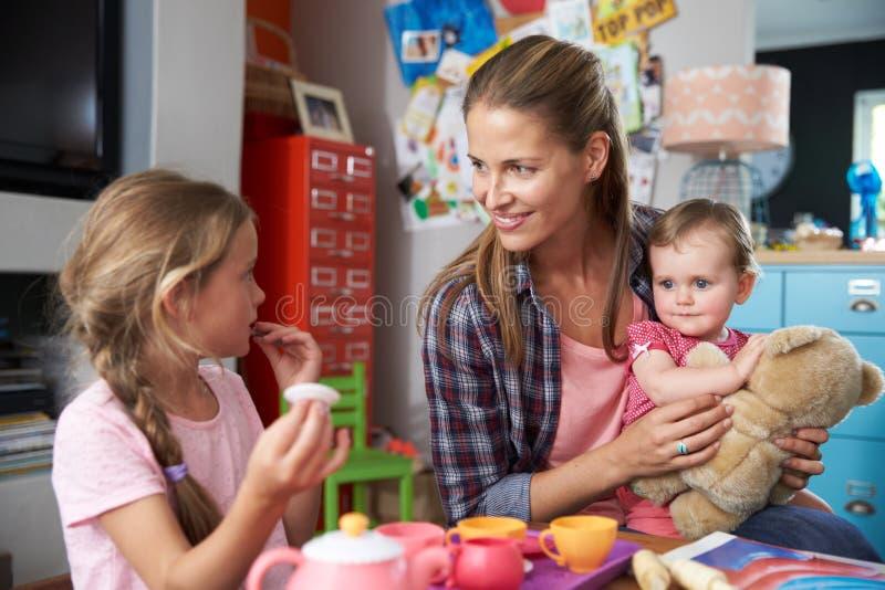 Moder som spelar leken med barn och leksaker i sovrum royaltyfri bild