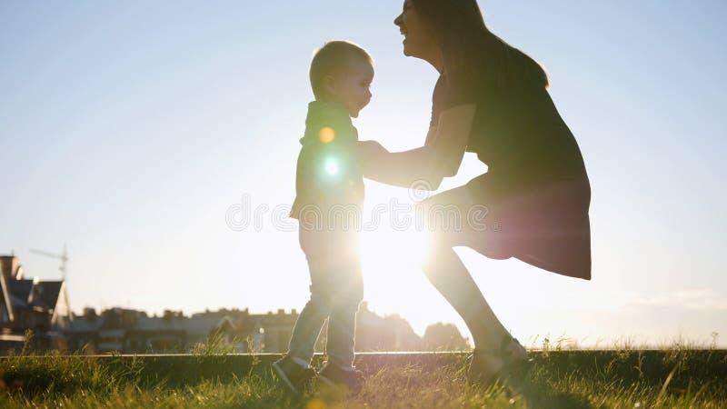 Moder som spelar med den lilla sonen på solnedgången - kast barnet arkivbilder
