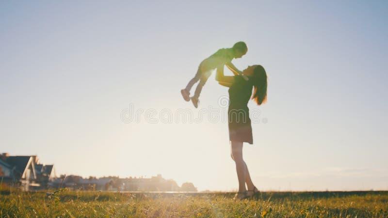 Moder som spelar med det lilla barnet på solnedgången - kast sonen fotografering för bildbyråer