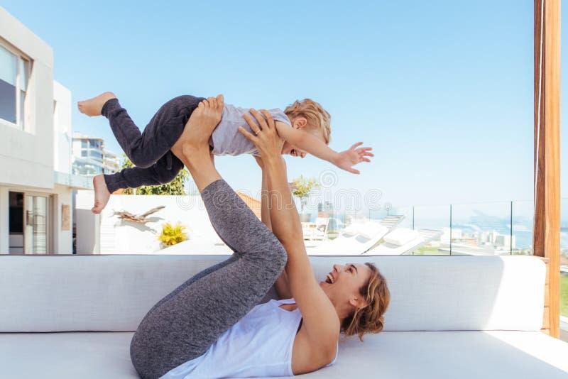 Moder som spelar med sonen på soffan royaltyfri foto