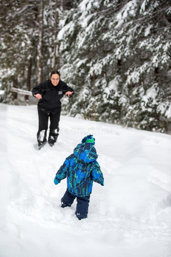 Moder som spelar med sonen utanför i snön royaltyfria foton