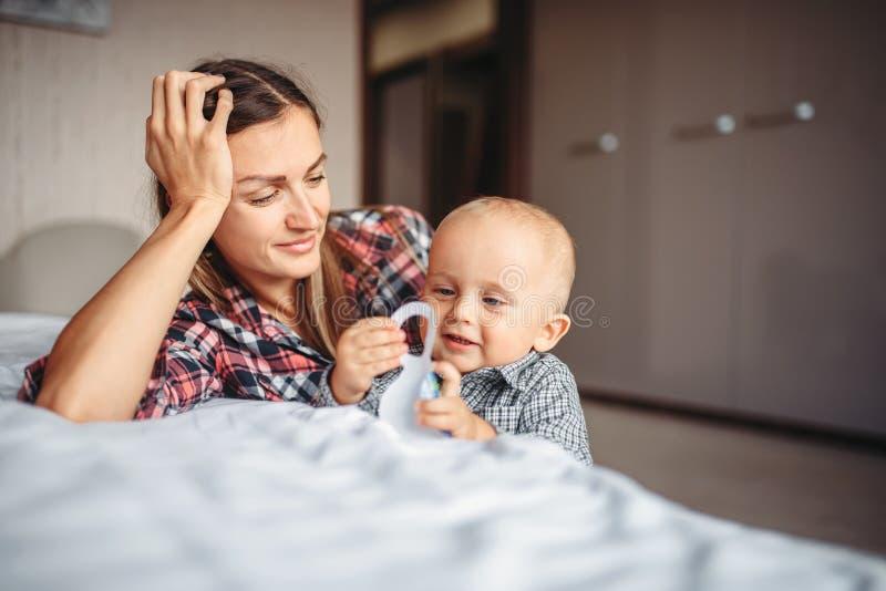 Moder som spelar på säng med den lilla gossebarnet arkivbilder