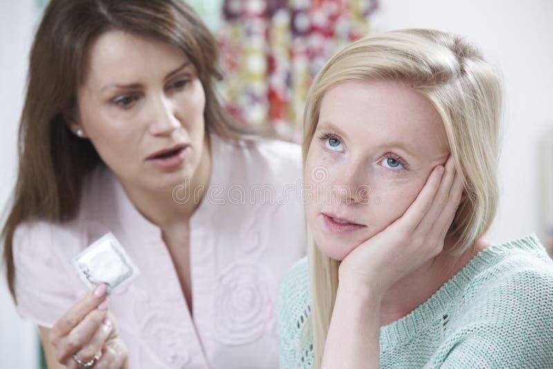 Moder som talar till den tonårs- dottern om det att använda preventivmedel fotografering för bildbyråer