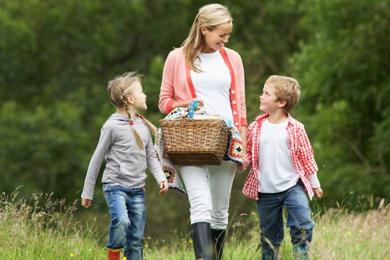 Moder som tar barn på picknick i bygd royaltyfria bilder