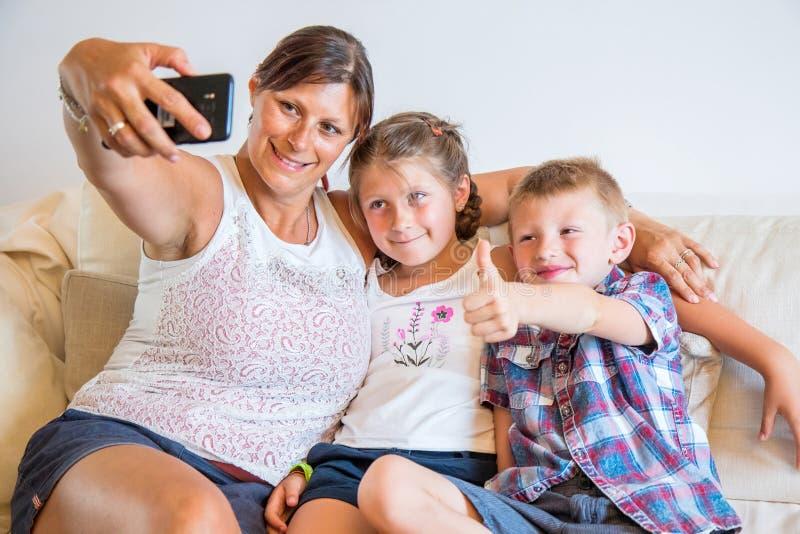 Moder som tar selfie med gulliga ungar på smartphonen, lycklig mamma som ler göra fotoet med sonen och dottern hemma royaltyfri bild