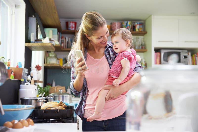 Moder som tar Selfie på hållande ung dotter för mobiltelefon arkivbild