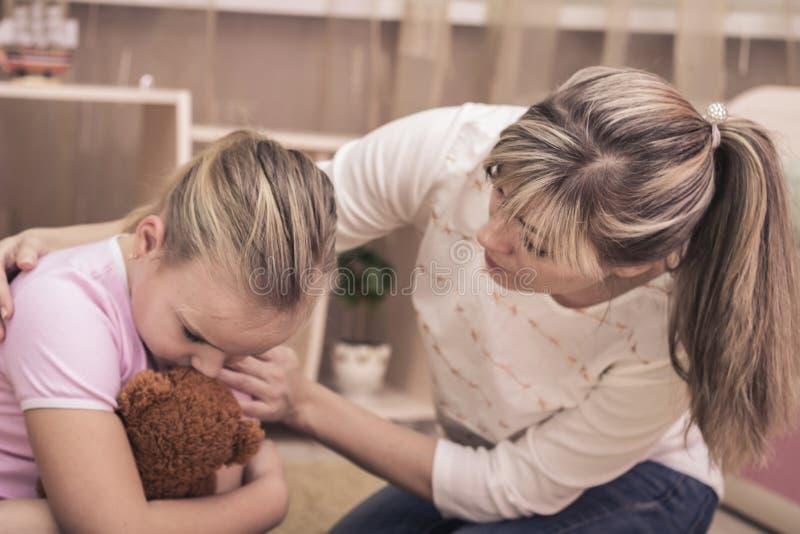 Moder som tröstar hennes ledsna tonårs- dotter Tonåringproblem trösta dotter henne moder royaltyfri bild