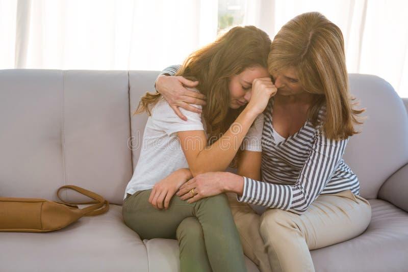 Moder som tröstar hennes tonårs- dotter fotografering för bildbyråer