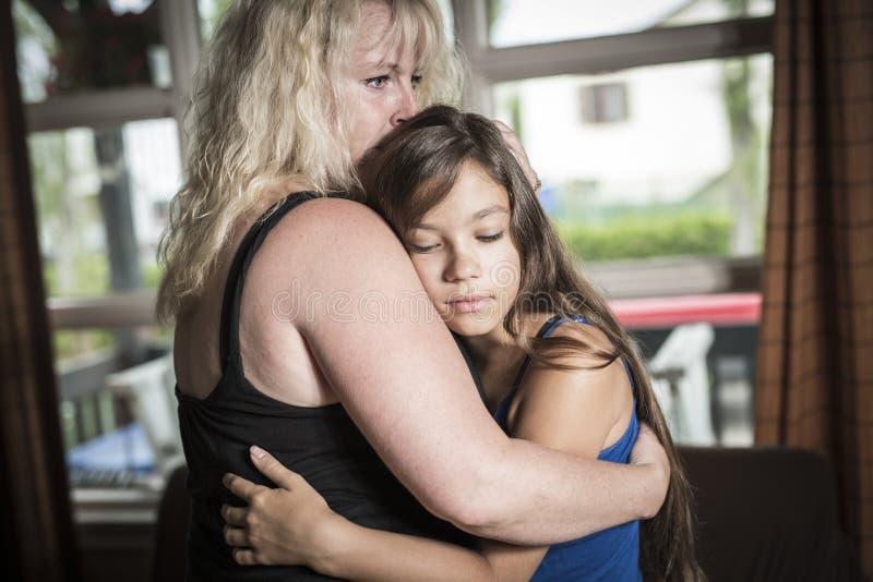 Moder som tröstar vardagsrum för tonårs- dotter royaltyfria bilder
