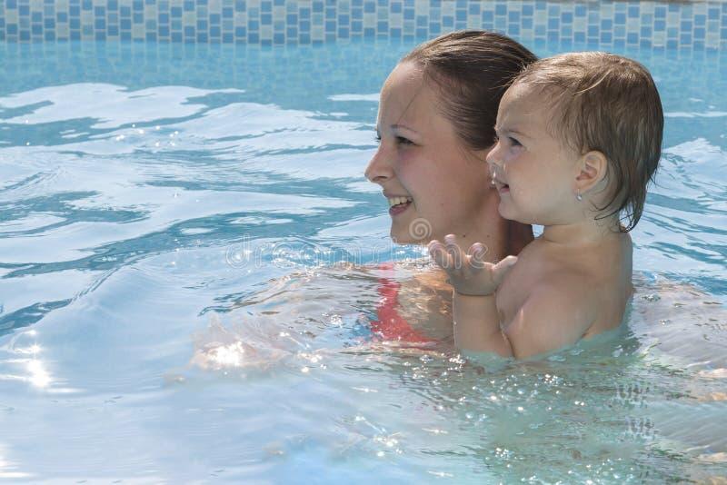 Moder som tycker om en pöl med barnet royaltyfri fotografi