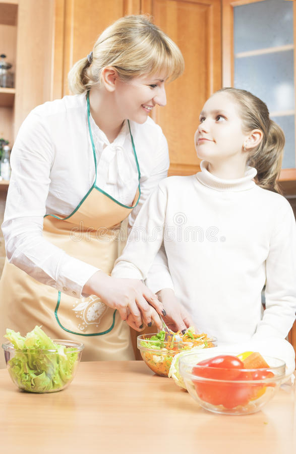 Moder som undervisar hennes tonårs- dotter att laga mat Salad i Kitchen arkivfoton