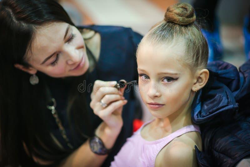 Moder som utgör till hennes dotter med skönhetsmedel, rodnader, ögonskuggor och borstar royaltyfri fotografi