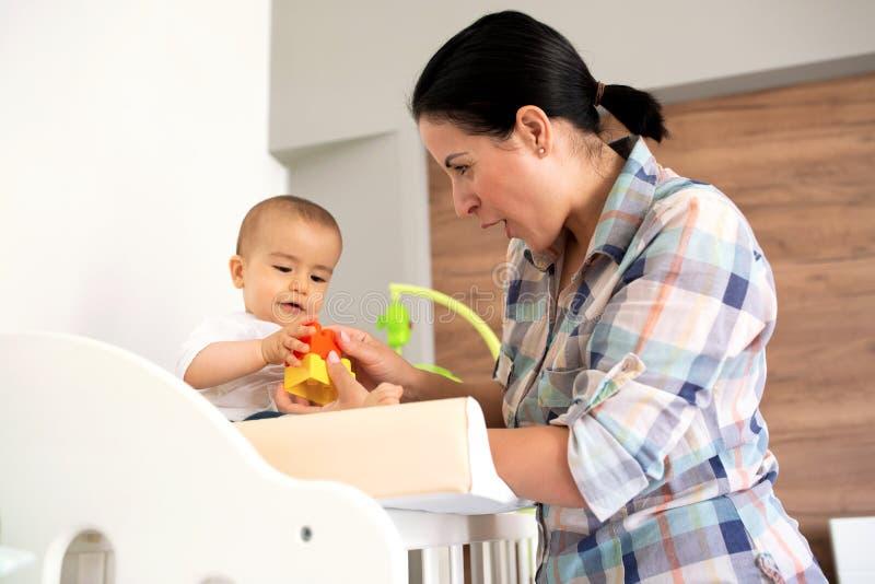 Moder som visar hennes spädbarn hur man monterar en leksak royaltyfria foton
