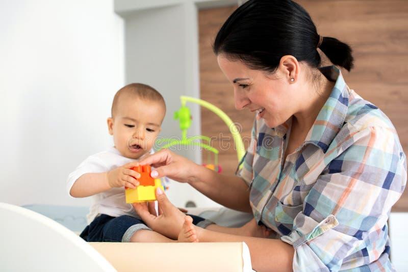 Moder som visar hennes spädbarn hur man monterar en leksak arkivfoton