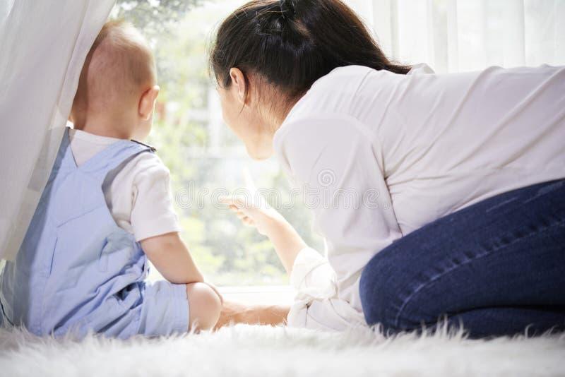 Moder som visar n?got i tr?dg?rd till hennes son arkivfoto
