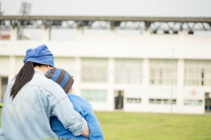 Moder, son i parkera, fotbollfält och gräsmatta royaltyfri foto