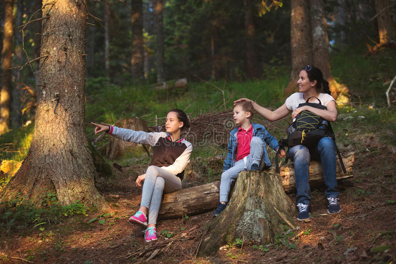 Moder, son och dotter som vilar i skog royaltyfri bild