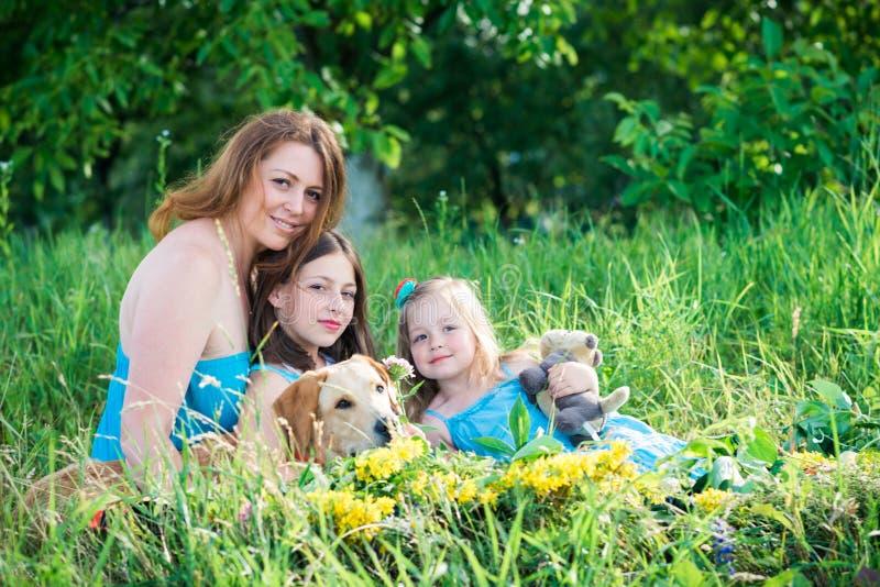 Moder, två döttrar och hund arkivbild