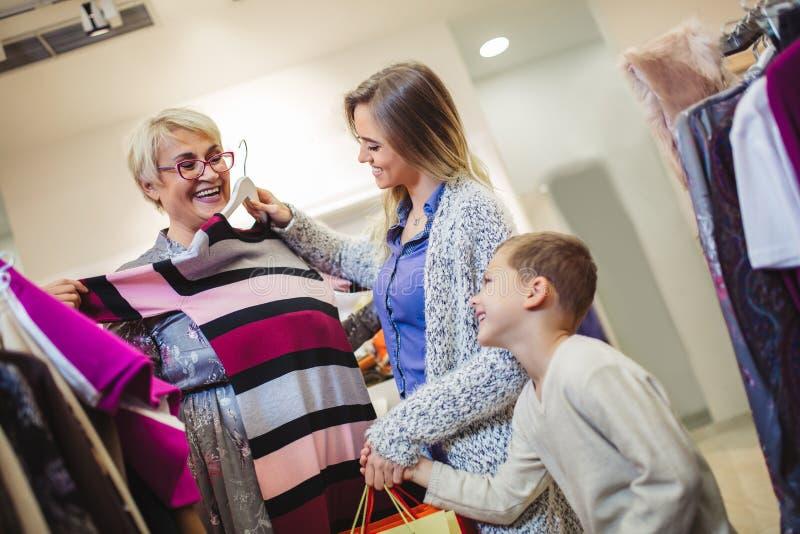 Moder, vuxen dotter och sonson i shoppinggalleria tillsammans royaltyfri foto