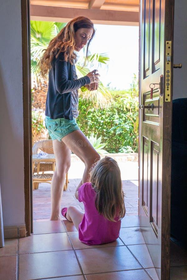 Moderanseende som talar till hennes dotter som sitter i dörröppning av a royaltyfri bild