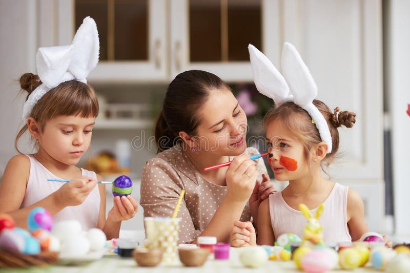 Moderattraktioner på dotters näsa, medan hon och hennes två lilla döttrar med vita kanins öron på deras huvud färgar royaltyfria foton