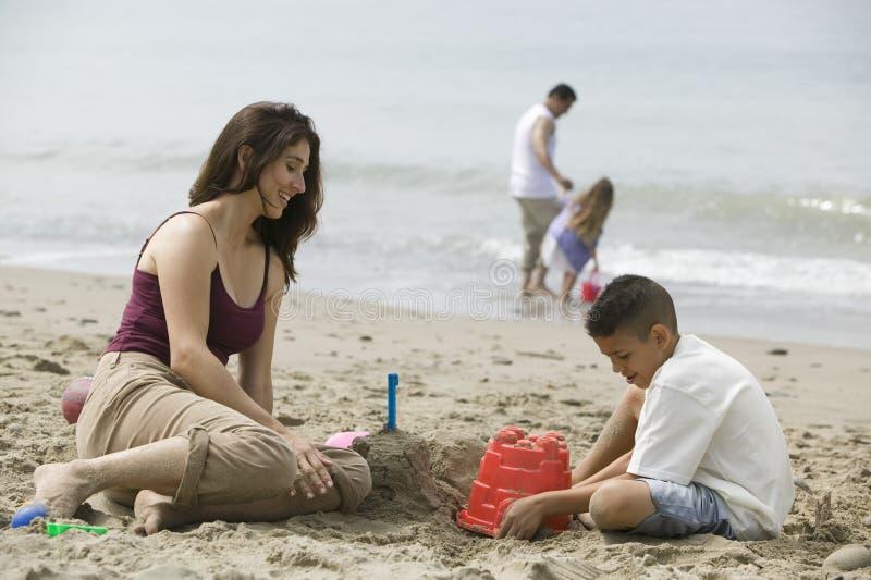 Moderbyggnadssandslottar med sonen på stranden royaltyfria bilder