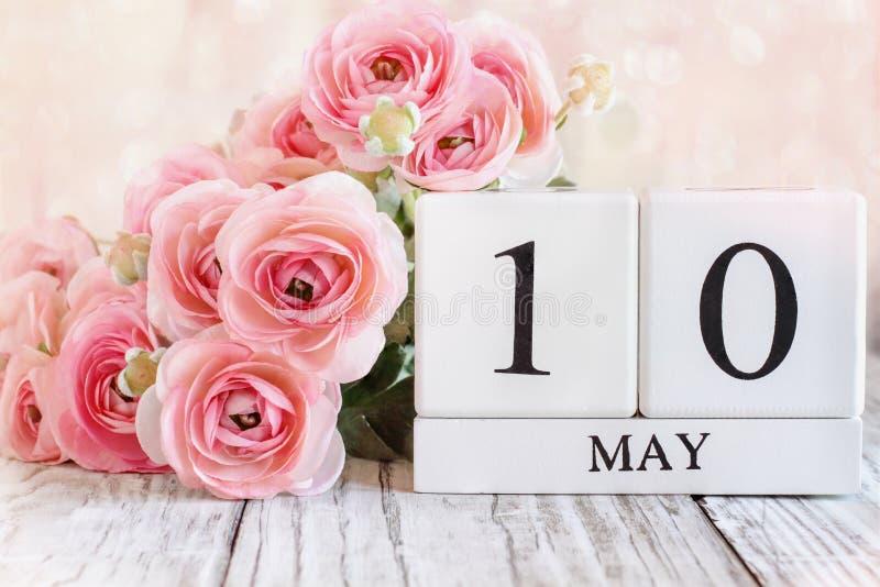 Moderdagskalender med rosa Ranunculus i bakgrunden royaltyfria bilder