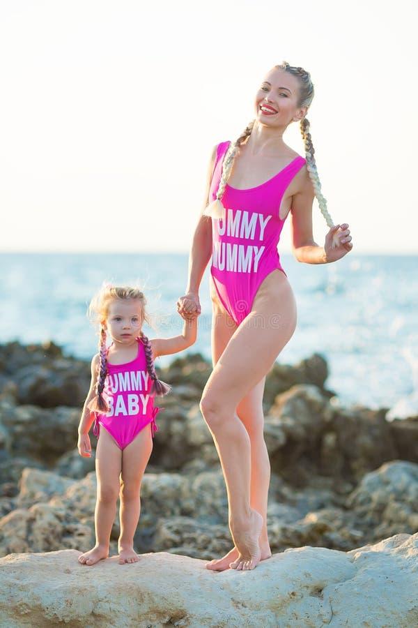 Moderdotter som har gyckel som vilar på den steniga stranden som bär rosa baddräkter Blond dam med flickan att tycka om sommartid royaltyfri fotografi
