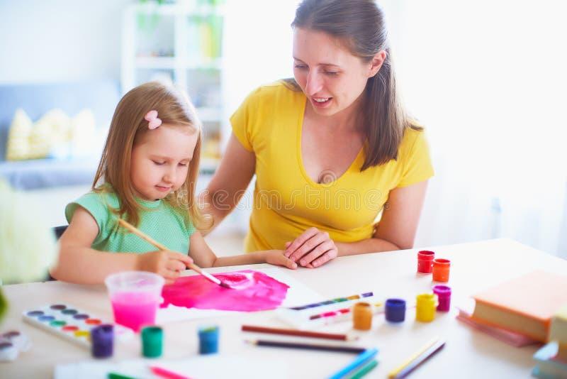 Moderdottern målar vattenfärgen på ett ark av papper som hemma sitter på tabellen i ett ljust rum royaltyfri fotografi