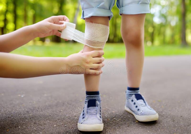 Moderhänder som applicerar antibacterial läkarundersökning, förbinder på barnets knä, når de har fallit ner arkivbild
