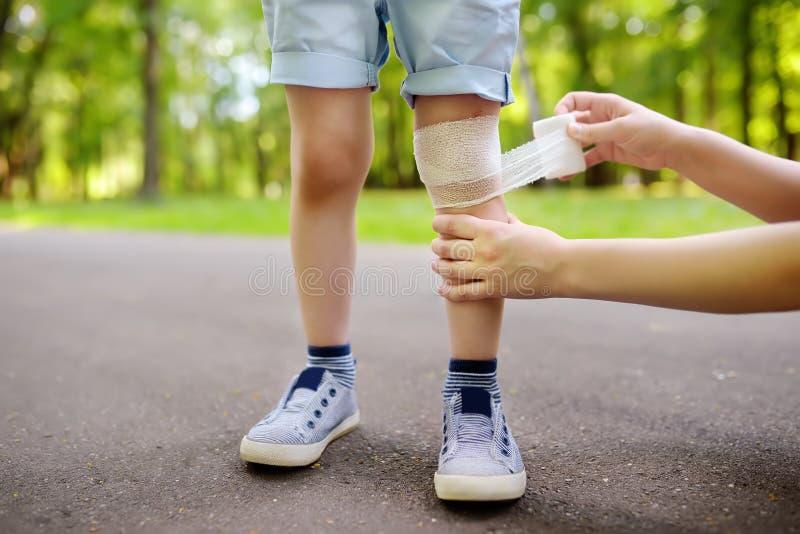 Moderhänder som applicerar antibacterial läkarundersökning, förbinder på barnets knä, når de har fallit ner royaltyfri bild