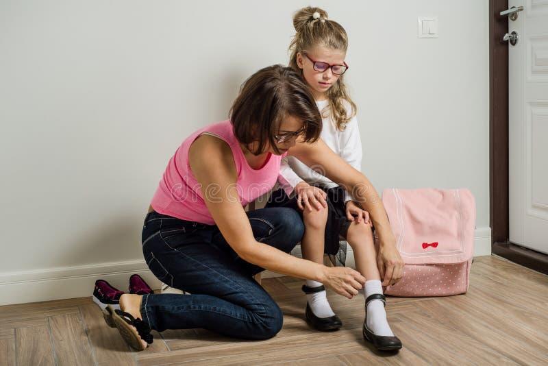 Moderhjälp som sätter skor på dotterfot arkivfoton