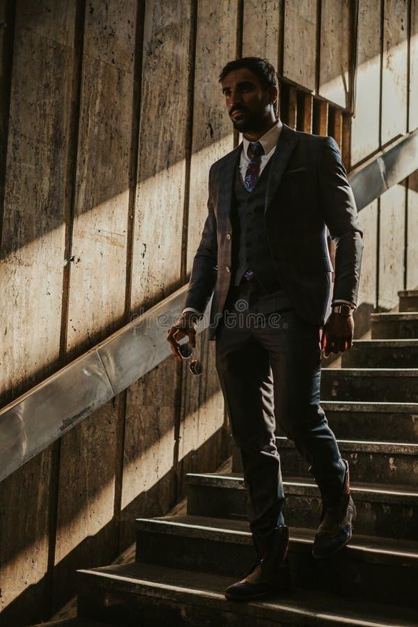 Moderiktig affärsman som går ner trappan royaltyfri bild