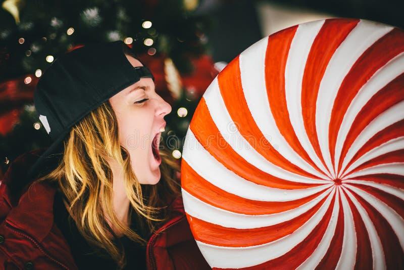 Moderiktig charmig flicka i det röda omslaget som bär det stilfulla locket som biter den gigantiska klubban arkivbilder